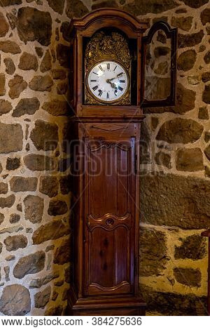 Old Vintage Antique Bronze Clock And Utensil On Wooden Shelf, Stone Wall Background. Antiques Concep