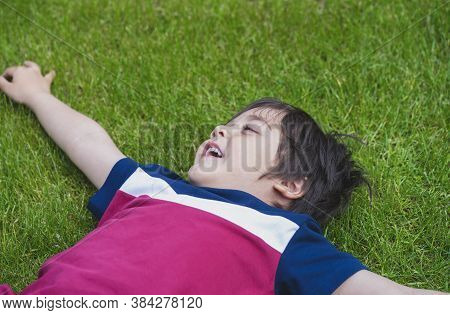 Top View Of  Young Boy Laying Down On Lawn In The Park, Cropped Shot Active Child Closing His Eyes A