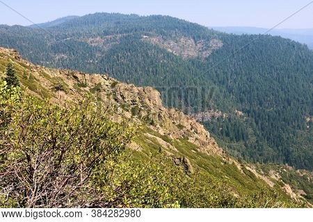 Lush Mountain Ridges With Rocky Crags Surrounded By Alpine Chaparral Shrubs Overlooking Temperate Pi