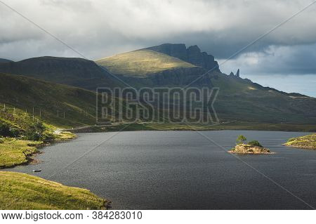 Scenic View Of Loch Fada With A Small Islet And A Silhouett Of Old Man Of Storr Rock Formation In Ba