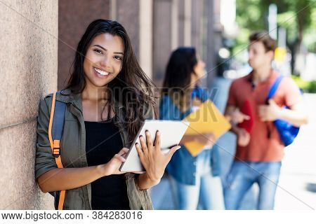 Laughing Mexican Student With Tablet Computer And Friends In Background In Front Of University Build