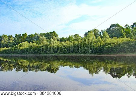 Landscape With Summer River. Trees And Bushes Are Reflected In Water Of River. Summer Forest. Water