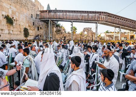 JERUSALEM, ISRAEL - SEPTEMBER 26, 2018: Jews praying wrapped in festive white Talit. The blessing of the Cohanim. Touching ceremony at the Western Wall. The concept of pilgrimage