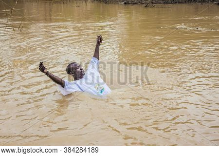 QASR El-YAHUD, ISRAEL - MARCH 2, 2020: Qasr el-Yahud is the site of the baptism of Jesus Christ. Young man in a white baptismal shirt enters in the Jordan River. Baptism ceremony.