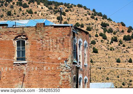 Abandoned Brick Building Surrounded By Arid Badlands Taken At A Rural Nevada Ghost Town