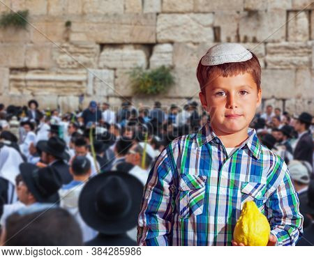 The greatest shrine of Judaism is the Western Wall of the Temple. Autumn Jewish holiday Sukkot. Beautiful Jewish boy with green eyes, in white skullcap, with citrus in his hand
