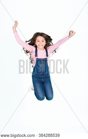 Happy Child In Jeans Overall Jump, Fashion. Small Girl With Long Brunette Hair Jump, Energy. Fashion