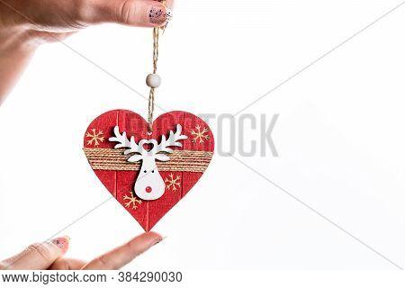 Hand Holding Heart Shaped Christmas Decoration Isolated On White.