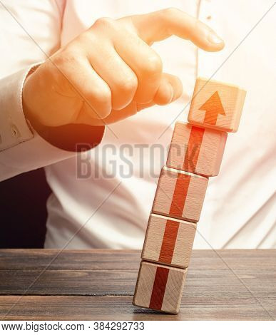 A Man Knocks Down A Tower Of Blocks With An Up Arrow. End Of Career, Destruction Of Progress And Ach