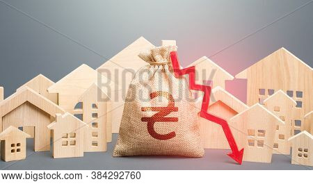 City Residential Buildings And Ukrainian Hryvnia Money Bag With A Red Down Arrow. Lower Mortgage Int