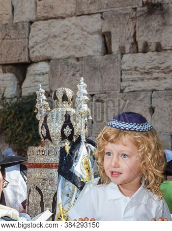Western Wall of the Temple. Autumn Jewish holiday Sukkot. The Jews brought the Torah Scroll for prayer. Handsome little boy with blond side curls and blue eyes, in skullcap