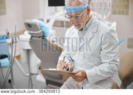 Busy Dentist Taking Notes While Sitting In His Office
