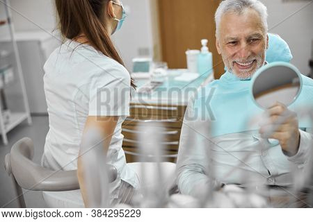 Gladsome Elderly Patient Smiling At Dentists Office
