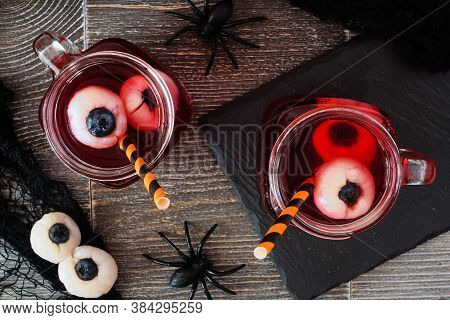 Spooky Halloween Eyeball Fruit Punch In Mason Jars. Top View Against A Dark Wood Background.