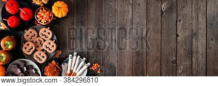 Rustic Halloween Treat Corner Border Over A Dark Wood Banner Background With Copy Space. Top View. A
