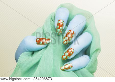 Blue Female Hand With Green Spotted Red Nails Is Holding Green Fabric On Yellow Striped Background,
