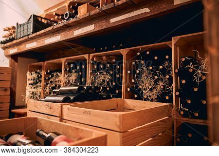 Bottles Of Wine Stored In Wooden Crates And Wine Racks