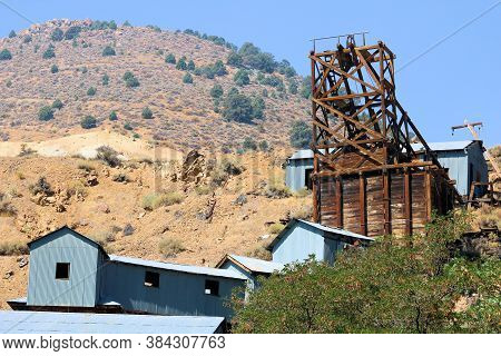 Historical Mine Besides Warehouses Surrounded By Arid Hills Taken In Virginia City, Nv