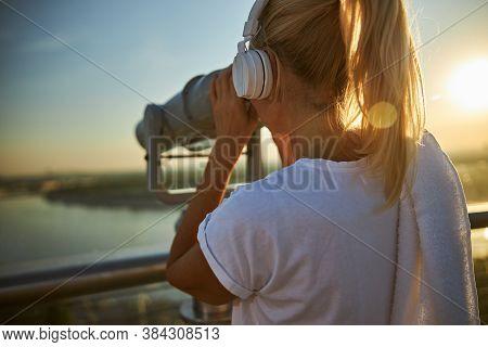 Woman In Headphones Using Observation Binoculars On The Street