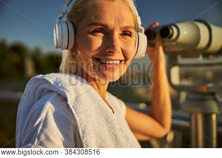 Cheerful Woman In Headphones Using Observation Binoculars On The Street