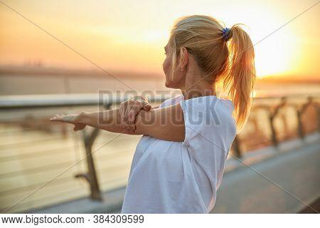 Female In A T-shirt Doing A Shoulder Stretch