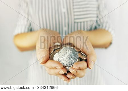 Woman Hand Holding A Handful Of Coins Bitcoins On White Background. Risky Currency Mining Concept An