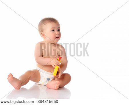 Little Naked Baby Wearing Diaper Playing With Toy Sitting On Studio Floor. Toddler Sucking Child In