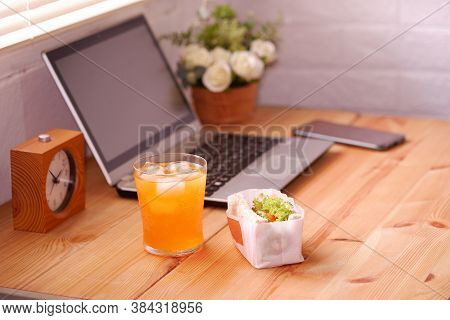Eat Sandwich And Orange Juice. During Work With Laptop Computer. Work And Eat Food At The Same Time.