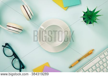 Coffee Cup At Center And Office Supplies As Keyboard Headphone Pen Stick Note Office Plants And Glas