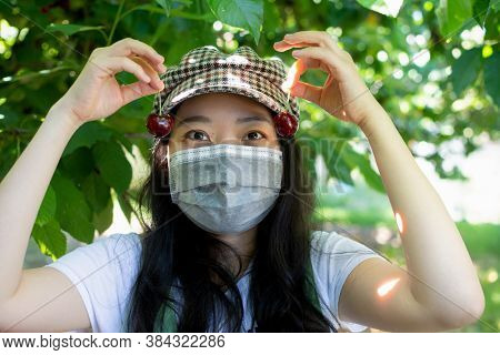 Asian Fruit Picker Holding Up Two Cherries In An Orchard