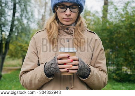 Caucasian Young Woman In Autumnal Casual Clothes Standing Alone, Looking Down, Holding In Hands Pape