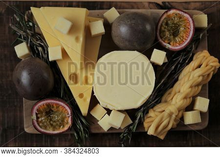 Cheese Platter With Fruits And Herbs.soft And Hard Cheeses Set, Passionfruit Cut, Rosemary On Dark A