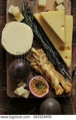 Cheese Platter With Fruits And Herbs.soft And Hard Cheeses Set, Passionfruit Cut, Rosemary On Dark B