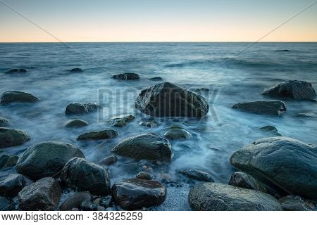 Calm Seascape Blue Sea Waters Shore, Rocky Coastline And Blue Evening Sun Over Water Horizon On Summ