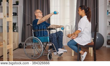 Elderly Man In Wheelchair Exercising During Rehabilitation With Support From Doctor. Disabled Handic