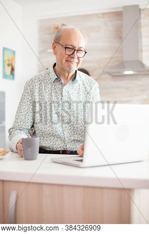 Old Man Smiling While Watching A Movie On The Laptop In The Kitcen. Daily Life Of Senior Man In Kitc