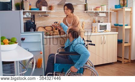Disabled Man In Wheelchair Helping Wife In Kitchen. Opening Refrigerator. Guy With Paralysis Handica