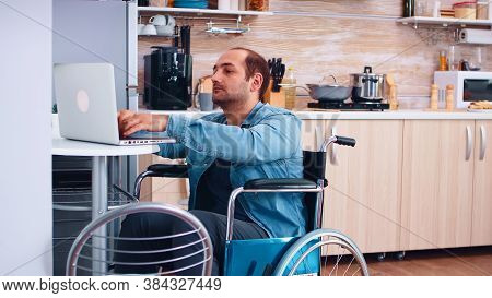 Handicapped Businessman In Wheelchair Using Laptop In Kitchen. Corporate Man With Paralysis Handicap