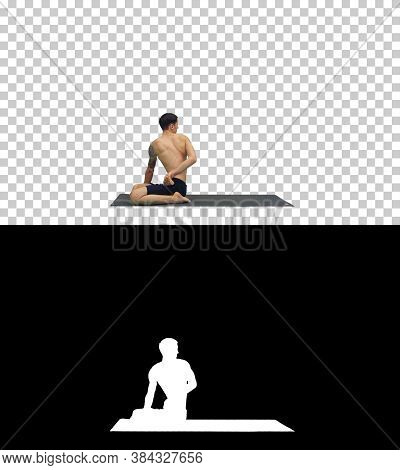 A Young Strong Man Doing Yoga Exercises Stretches Padmasana Legs, Alpha Channel