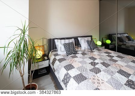 View Of King-size Bed And Bedsides With Lamps In Modern Bedroom. Interior In Light Tones.