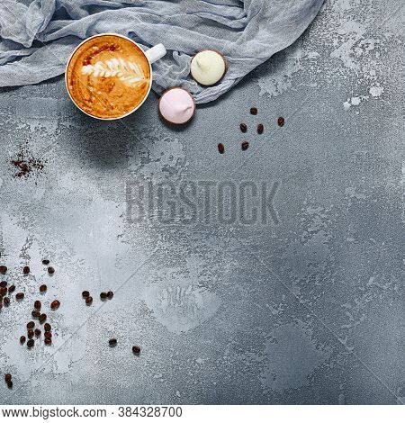Coffee drinks with appetizing foam top view. Cappuccino cups, coffee beans and cream pitcher flat lay on grey cement surface. Barista accessories composition. Hot beverages and desserts