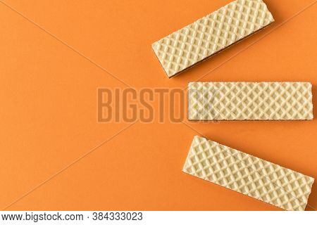 A Few Waffles With Chocolate On An Orange Background