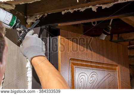 The Worker Foams And Insulates The Door, Uses A Carpenters Foam Gun, A Close-up Of The Work Process.