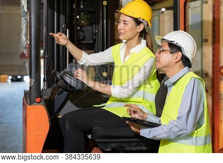 Female young asian warehouse forklift workers discuss about inventory to male warehouse manager in large distrubution warehouse background. Reopening business warehouse inventory and logistic concept