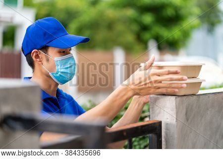 Asian deliver man with face mask in blue shirt handling food boxes and put in on the fence post of customer house as contactless food delivery. This can reduce coronavirus COVID-19 spreading.