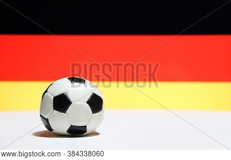 Small Football On The White Floor With Black Red And Yelow Color Of German Nation Flag Background. T