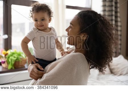 Smiling Sincere Biracial Woman Holding On Hands Curly Toddler.