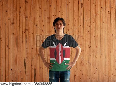 Man Wearing Kenya Flag Color Shirt And Standing With Akimbo On The Wooden Wall Background, Black Whi