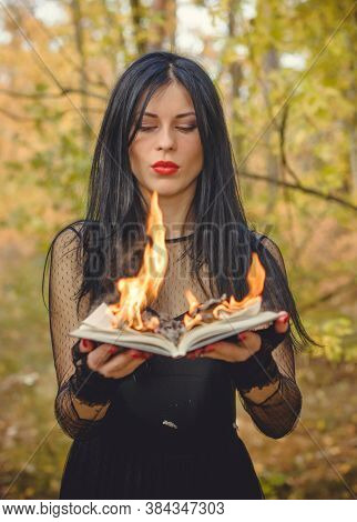 Halloween Witch In A Dark Forest. Beautiful Young Woman In Witches Modern Dress . Halloween Art Desi