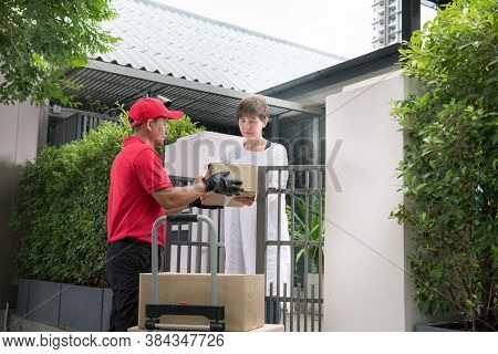 Asian Delivery Man In Red Uniform Delivering Parcel Boxes To Woman Recipient At Home